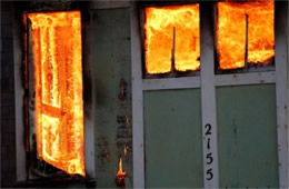 Structure Filled with Fire Inside Seen Through Windows and Doors